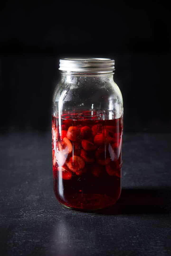 64 ounce jar with bourbon and cherries floating in it