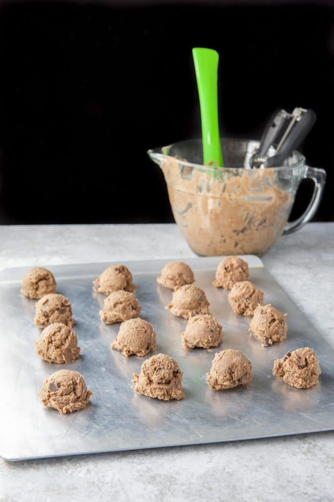 A cookie sheet with balls of chocolate cookie dough in front of a bowl of dough in the back