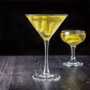 The classic martini glass filled with the cocktail with lemon twists in it - square