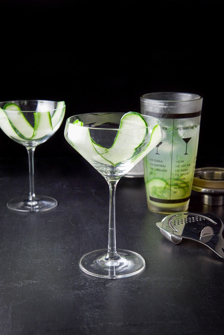 Thin cucumber slices draped in the glasses with the shaker filled with the cocktail in the background