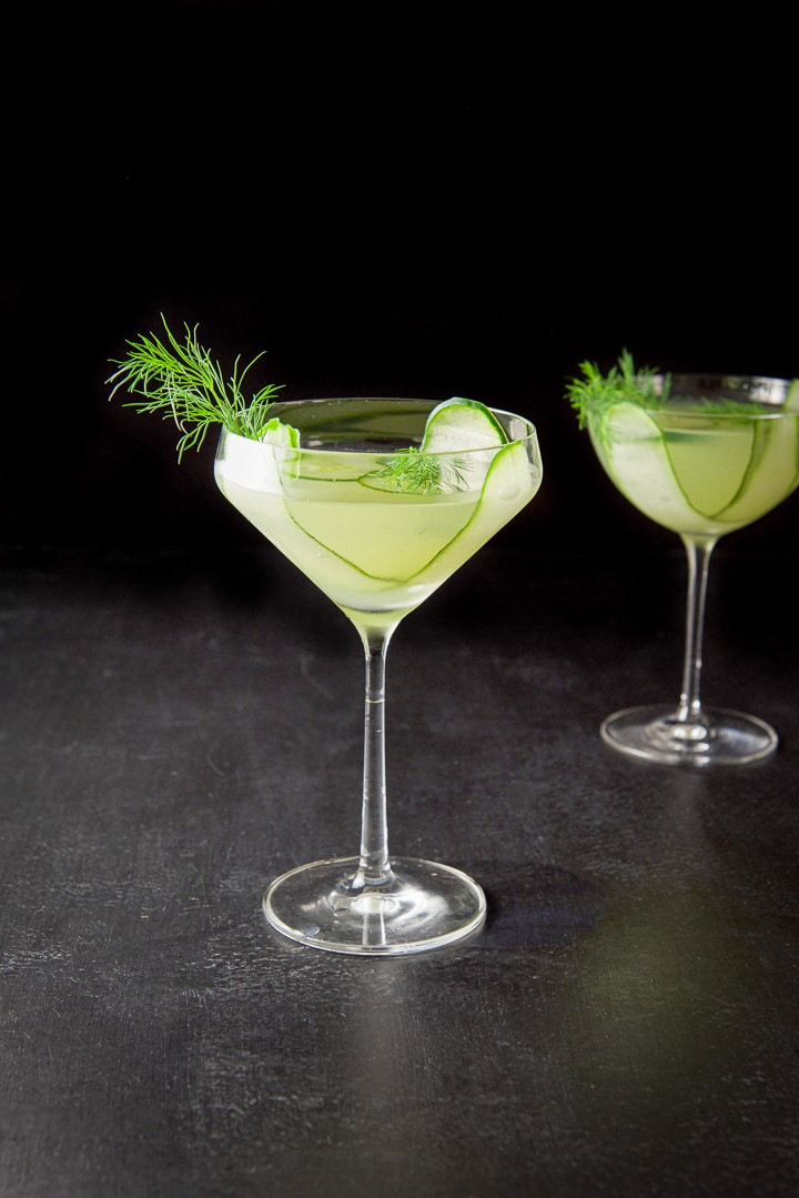 Curved glass with the cucumber martini in front of the bowl glass in the background. There is cucumber and dill as garnish