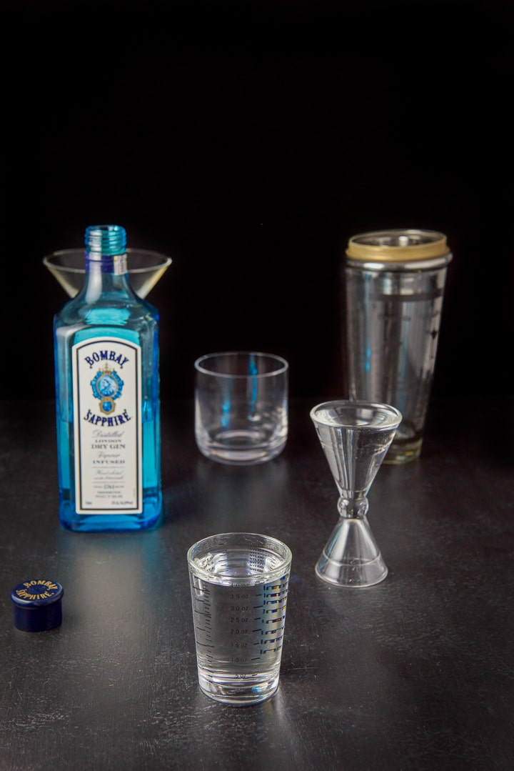 Gin measured with the bottle, shaker and glasses in the background