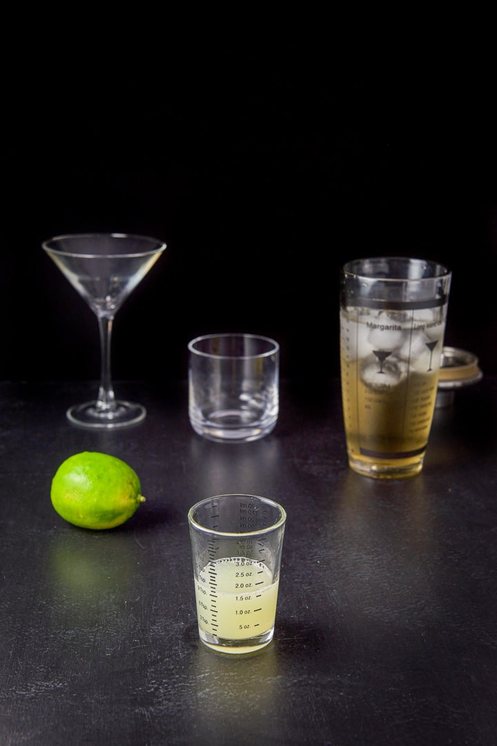 Lime juice poured out with a lime, shaker and glassware in the background