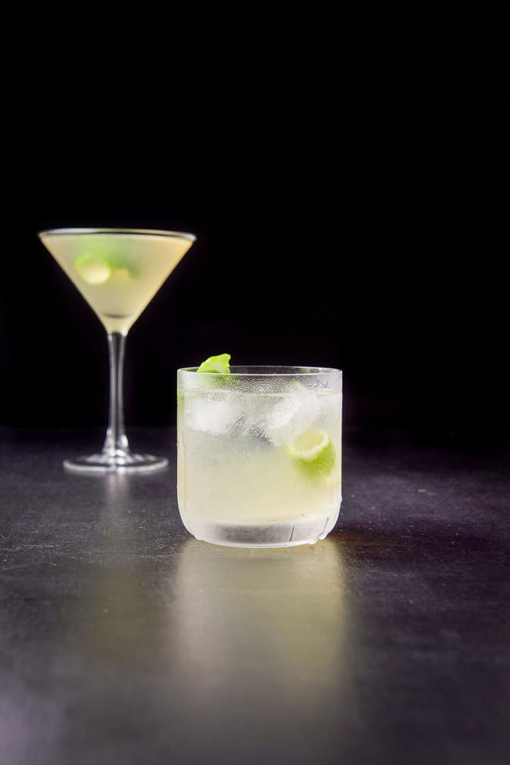 Vertical view of the gimlet in the old fashioned glass in front of the classic martini glass