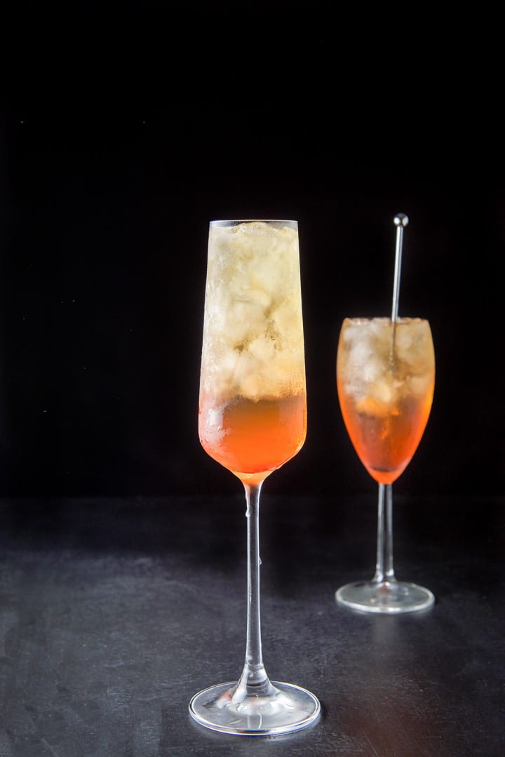 Tall champagne glass filled with the orange cocktail in front of the other glass with the stirrer