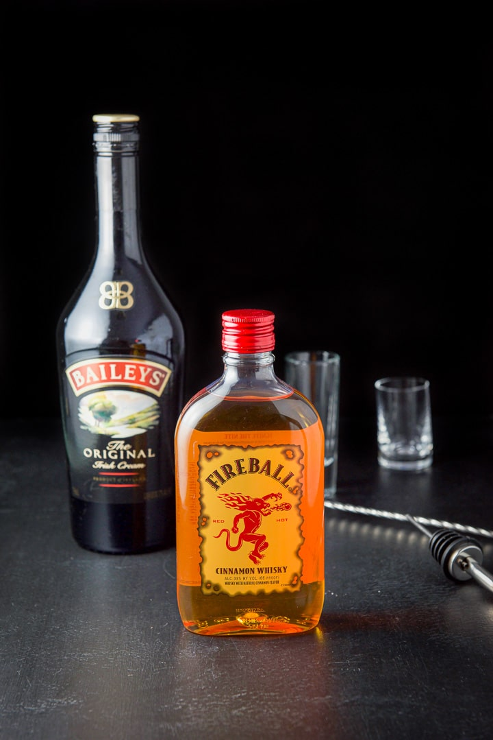 Fireball whiskey and Baileys Irish cream along with a pourer, spoon and glassware on the table