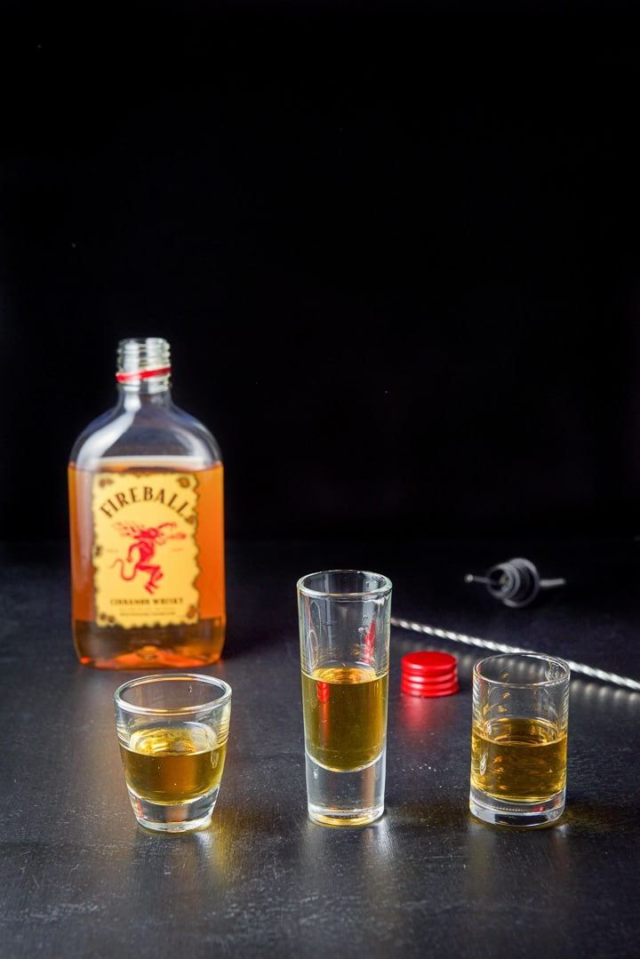 Fireball whiskey poured in the three shot glasses with the whiskey in the background