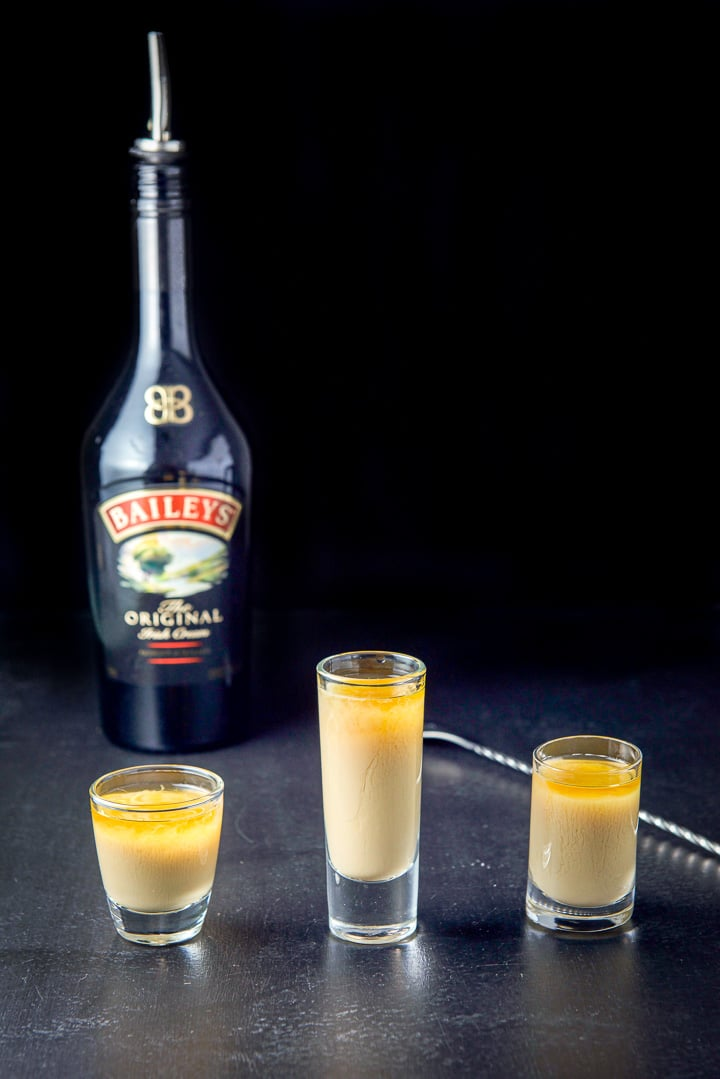 Irish cream layered into the glasses with the spoon and bottle in the background