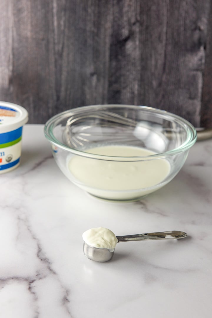 Sour cream measured out in front of the bowl of cream