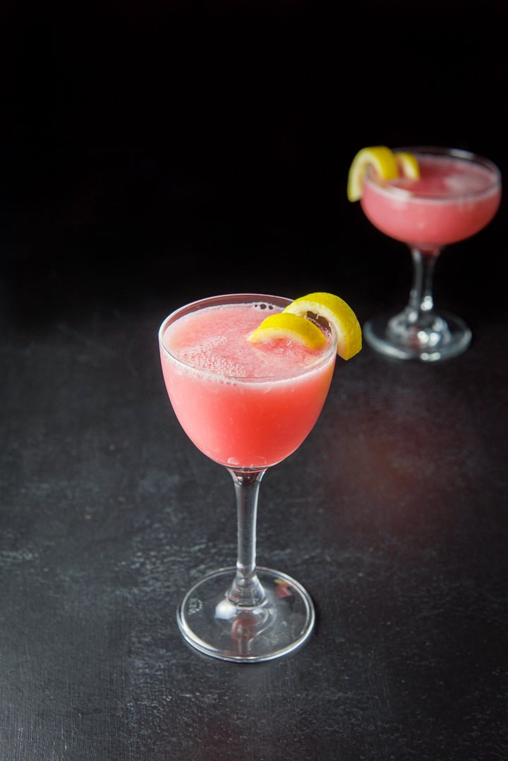 Tall martini glass in front filled with the pink lady cocktail