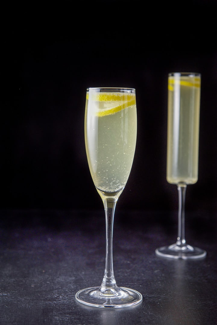 Vertical view of the classic champagne glass in front of the straight glass. You can see bubbles and the lemon twists