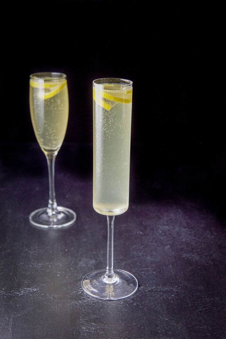 The thin champagne glass filled with the drink, the classic glass is behind it and both have lemon twists in the glasses