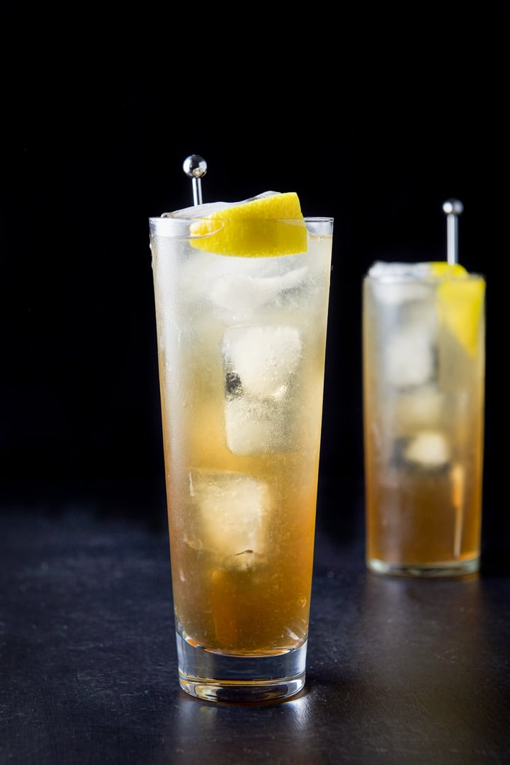 Vertical view of the wider glass filled with the potent cocktail with a lemon wedge and stirrer