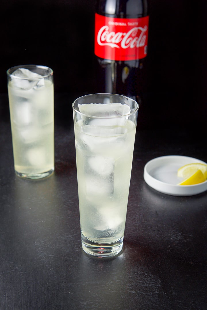 Everything but the coca cola poured in the glasses with a few lemon wedges in a white dish