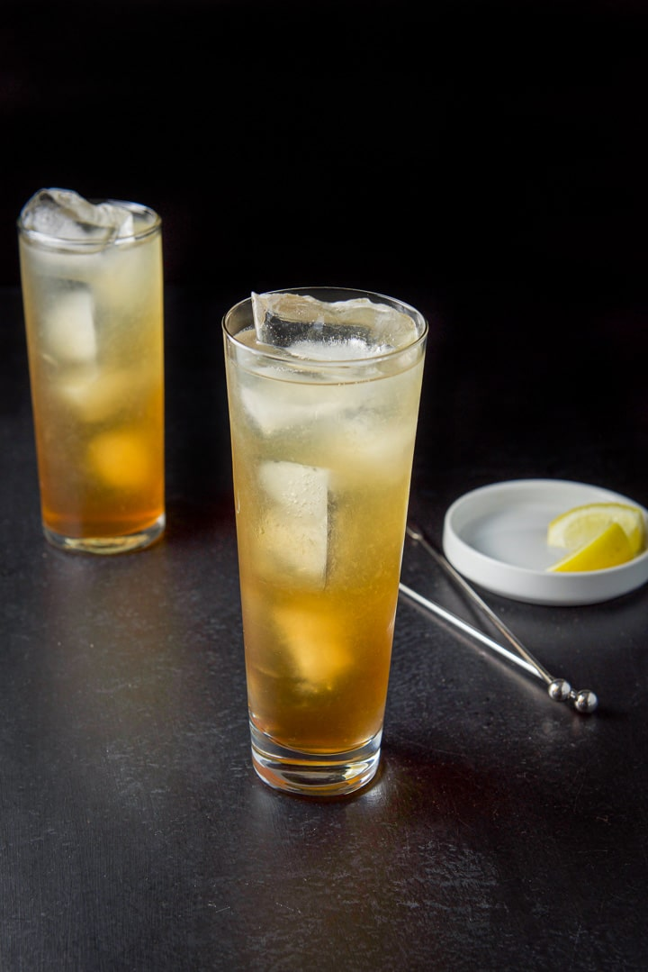 Two straight glasses filled with the potent amber cocktail with two stirrers and lemon garnishes in the background