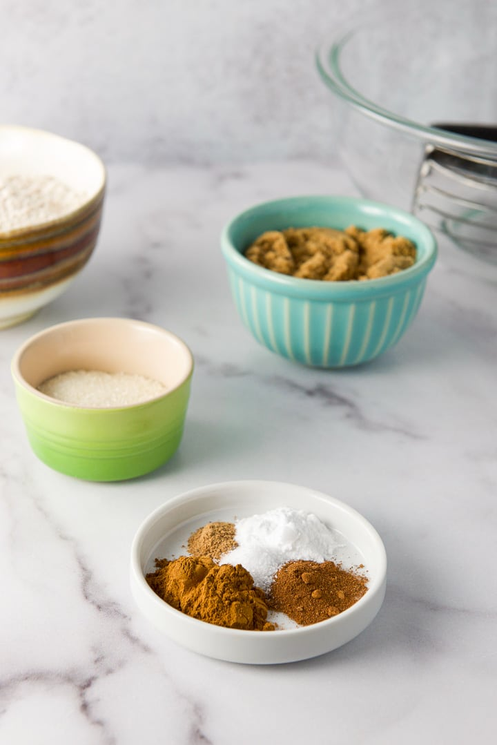 Spices, sugars and flour and a glass bowl in the background