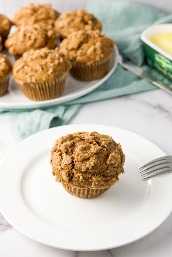 Close view of a pumpkin muffin on a white plate with more on a bigger plate behind it