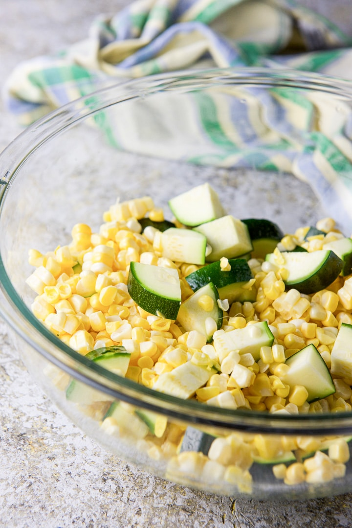 Chunked zucchini and corn off the cob in a glass bowl with a dish towel in the background