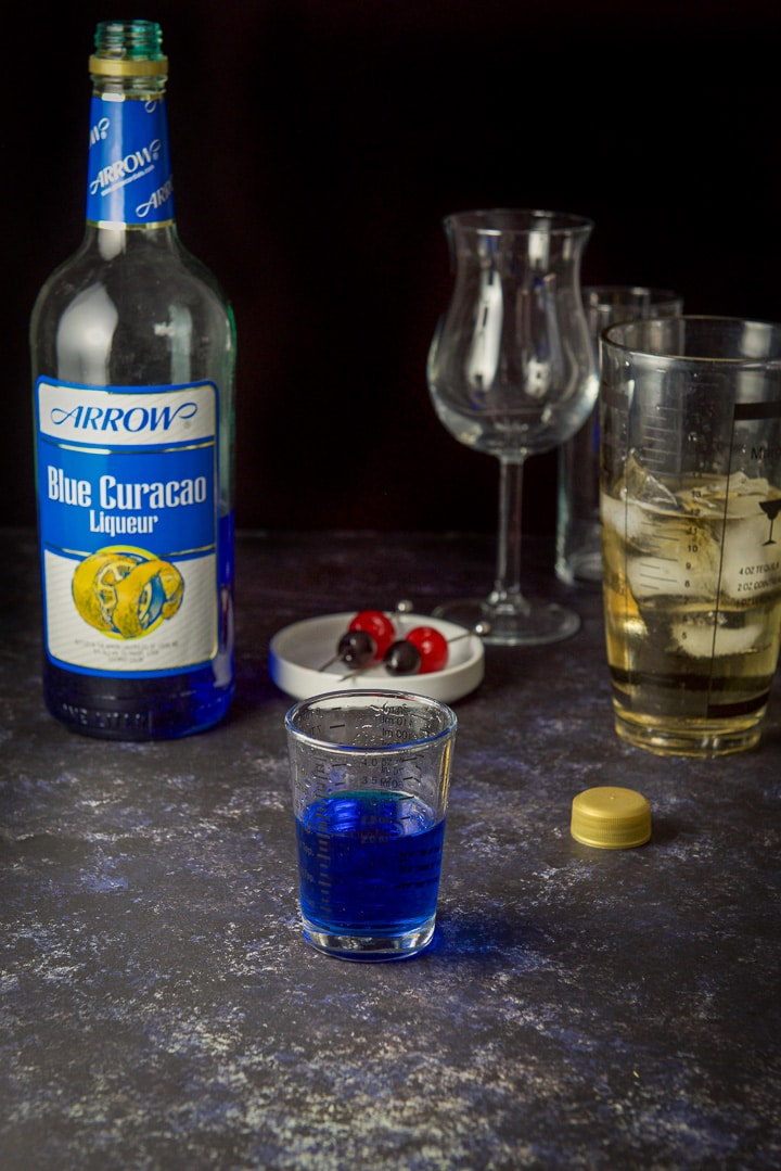 Blue curacao poured out for the sweet poison cocktail