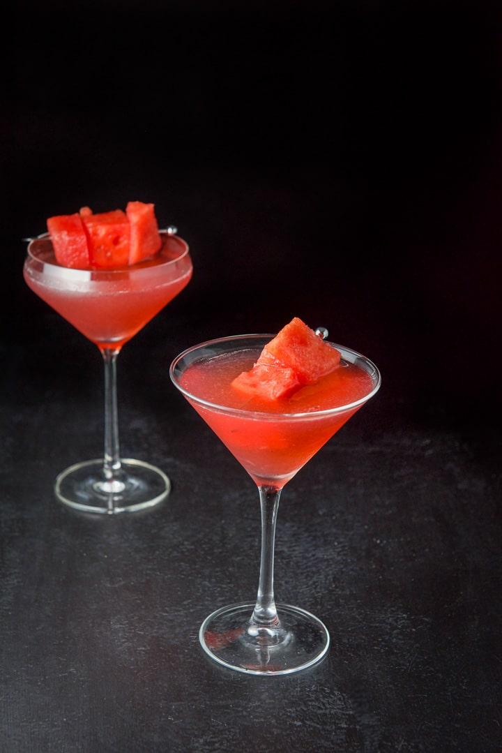 The classic martini glass in front of the shaped one filled with the cosmo with some chunks of watermelon in it