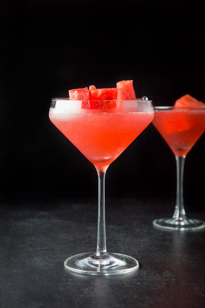 Vertical view of the fancy martini glass filled with the cosmo with watermelon chunks garnishing them