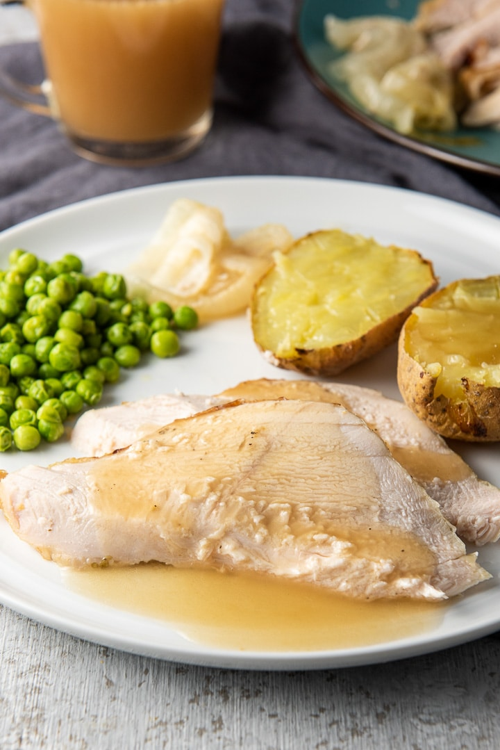 Turkey breast slices on a plate with gravy, potatoes and veggies