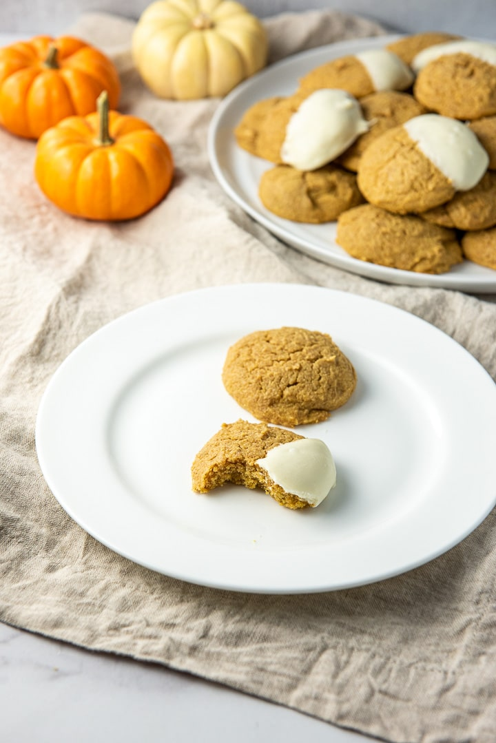 One of the cookies with a bite taken out of it and on a plate with a whole one behind it