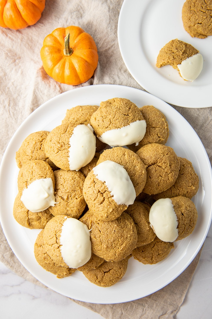 Overhead view of the big plate of cookies with small pumpkins and a small plate with cookies on it as well