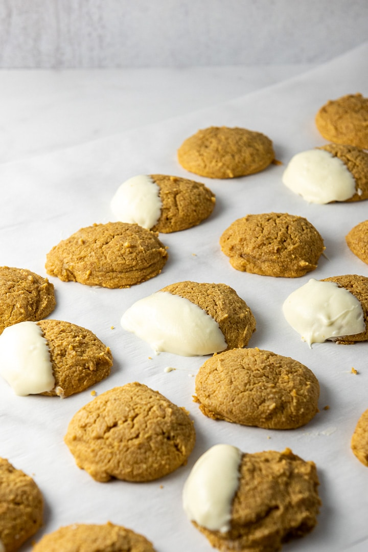 Parchment paper filled with pumpkin cookies, some dipped in white chocolate
