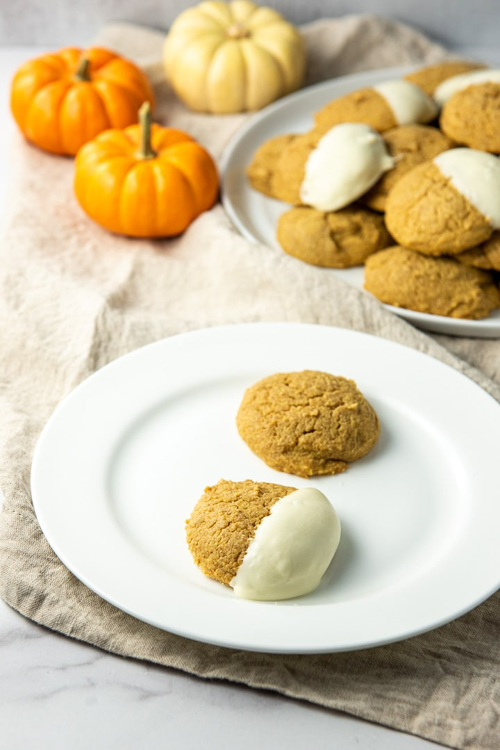 Close up of a plate of two pumpkin cookies, one plain and one dipped in white chocolate