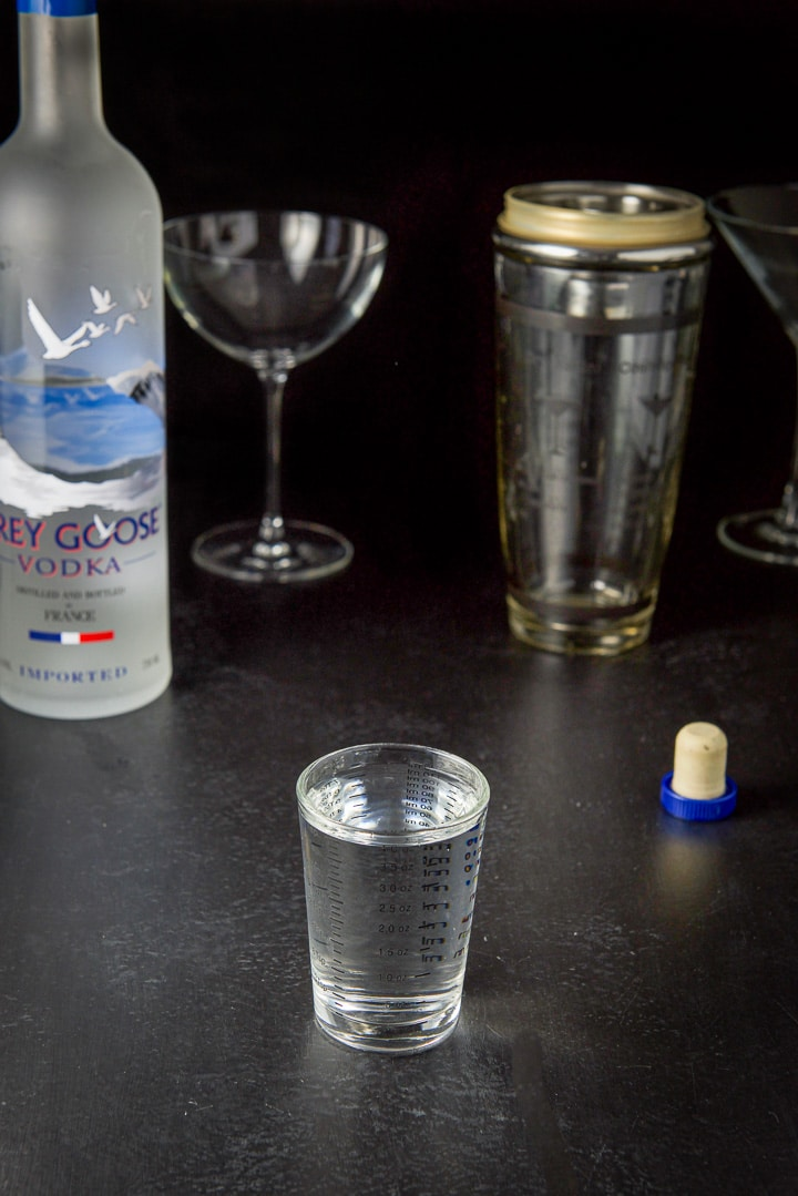 Vodka poured out with the bottle, shaker and glasses in the background