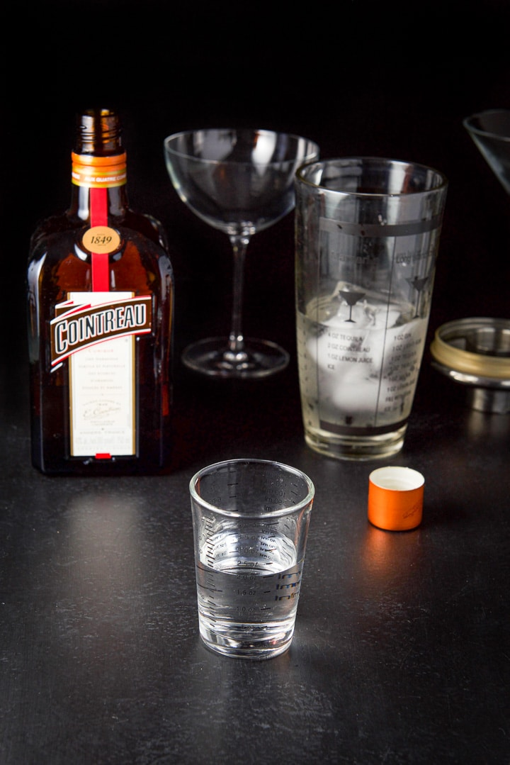 Cointreau poured with the bottle, shaker and glasses in the background