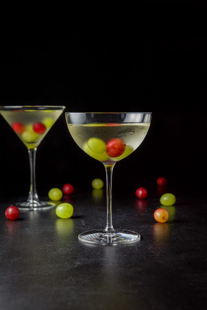 Vertical view of the wide glass filled with the cosmo with grapes in the glass and on the table