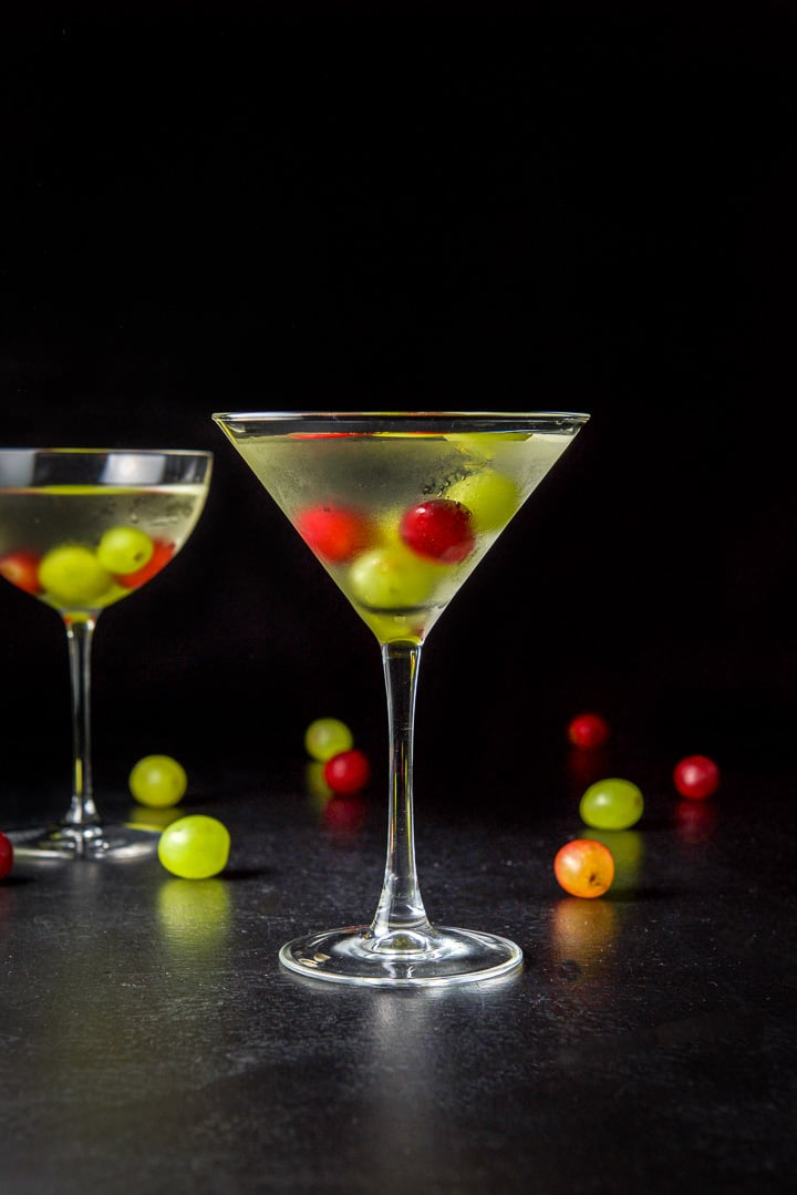 Vertical view of the classic martini glass filled with the grape cosmo with grapes in it and strewn on the table