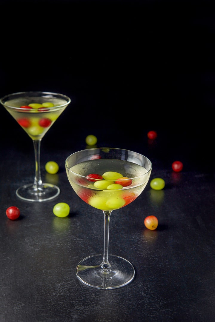 The curved glass in front of the classic martini glass. Both are filled with the cosmo with grapes in the drinks and on the table