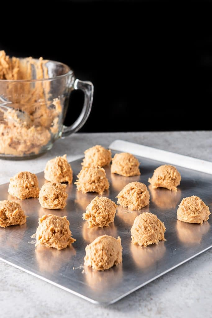 Balls of butterscotch cookies batter on a cookie sheet with the glass bowl in the background