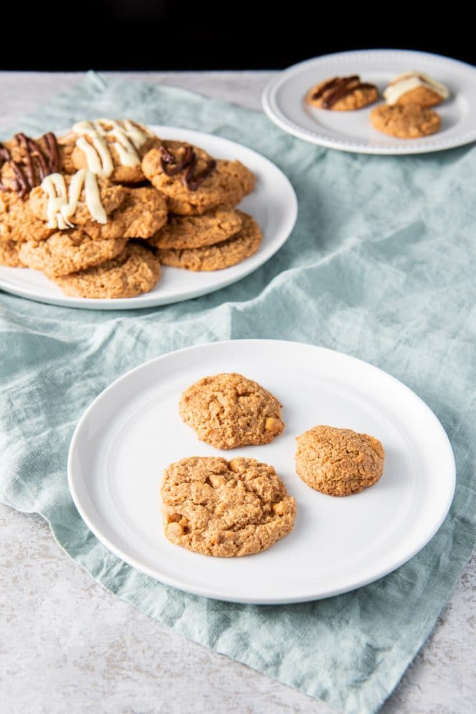 Three different sized cookies on a white plate with the big plate of cookies behind it