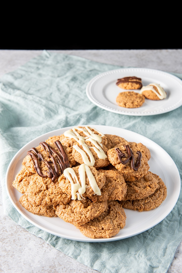 A pile of cookies on a big white plate with a few cookies on another plate behind it