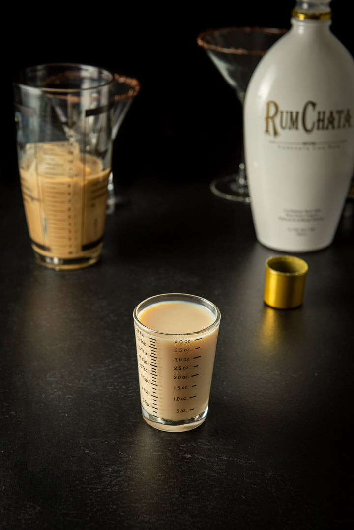 RumChata measured out with the bottle in the background