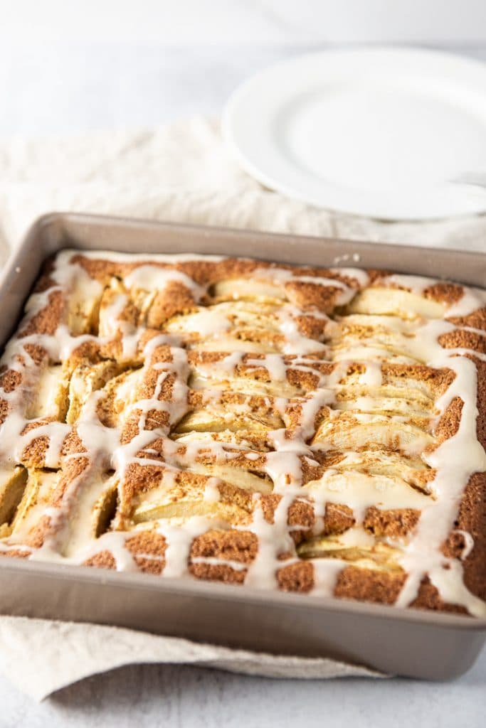 Newly frosted apple cider cake in a square pan