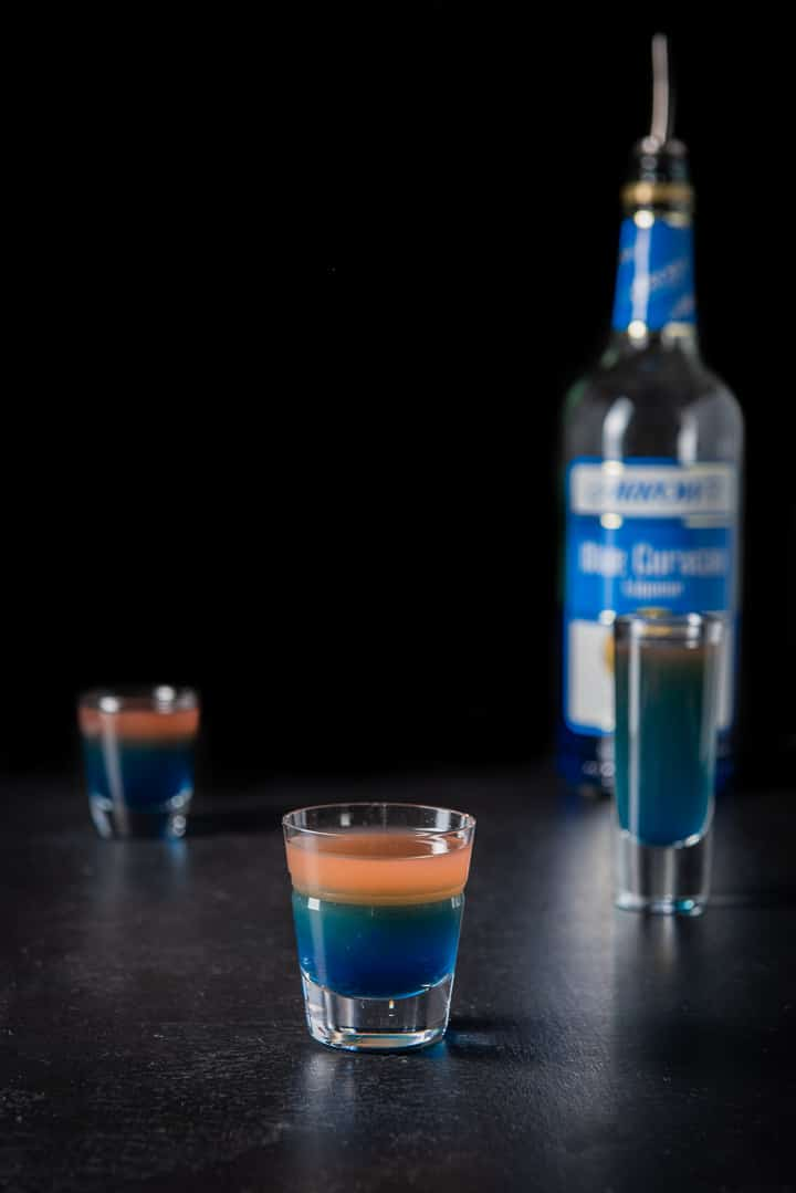Blue curacao poured into the beveled glass with the layers clear, there is the bottle in the background