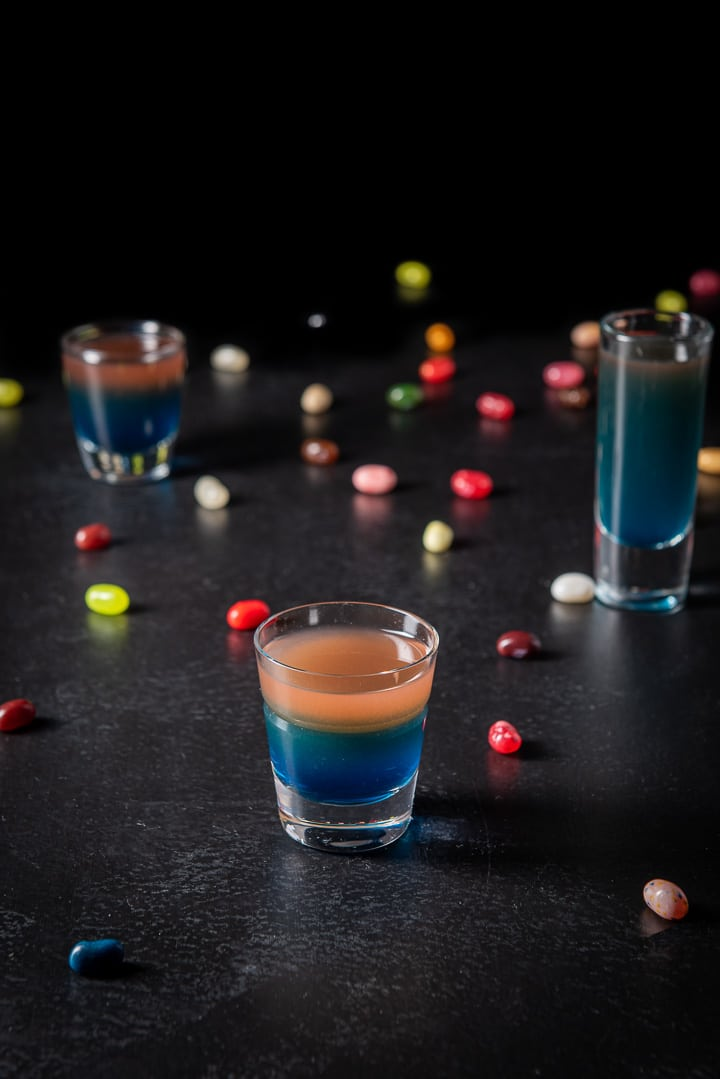 Higher view of the beveled glass filled with the shot with the other glasses and jelly beans in the background