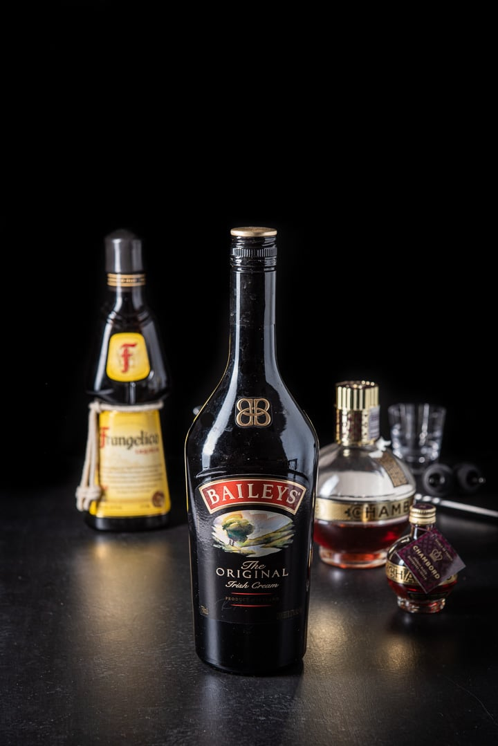 Baileys Irish cream, Frangelico and Chambord on a black table
