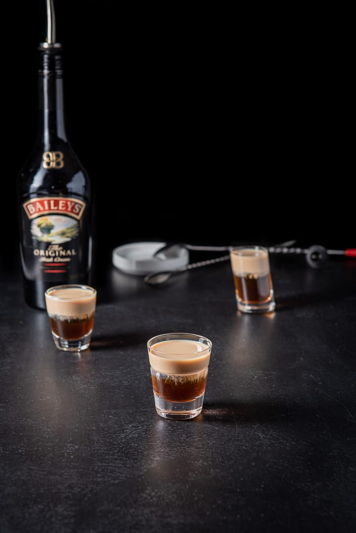 Baileys layered in the glasses with the bottle in the background