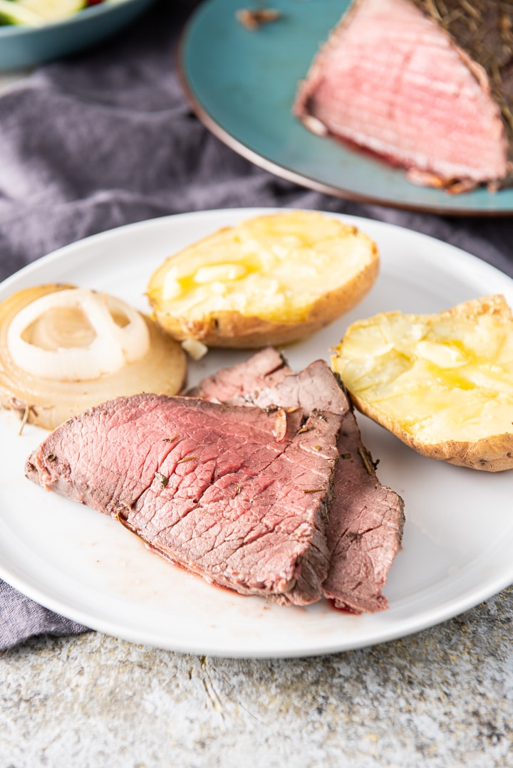 A white plate with a few pieces of roast beef with a potato and onions