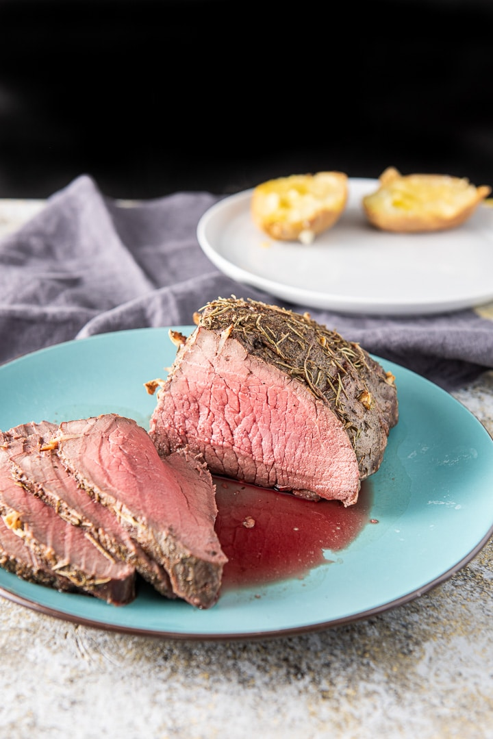 Slices of the roast beef on a blue plate with a plate of potato in the background