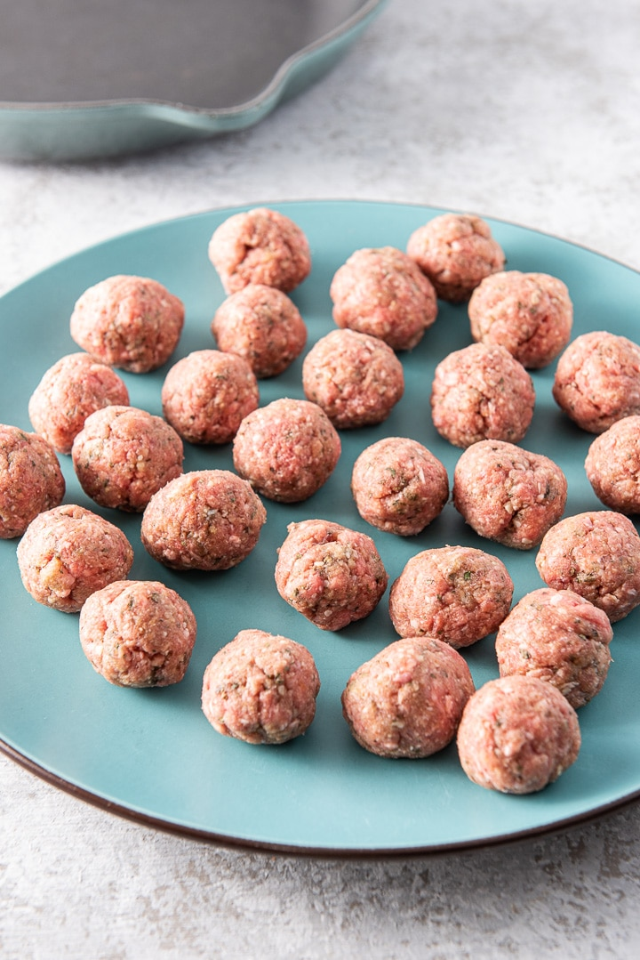Raw meatballs on a blue platter with a cast iron pan in the background