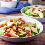 Colorful salad in two shallow bowls with pomegranate seeds in the background - square