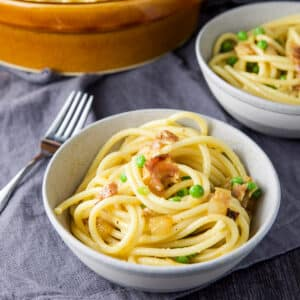 Pasta carbonara in a grey bowl with a fork and another bowl in the background - square