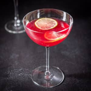 Square photo of the pomegranate cocktail with two lime wheels floating